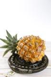 Mogna saftiga nya behandla som ett barn ananas på den svarta stenen Royaltyfri Bild