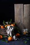 Mogna saftiga orange citrusfrukter i en korg, rottingsocker i en can, för framställning av driftstopp Mörk bakgrund, selektiv fok Arkivfoton