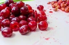Mogna saftiga röda körsbär gjorde full av hål royaltyfria foton