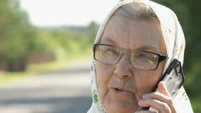 Mogna samtal för gammal kvinna genom att använda smartphonen utomhus arkivfilmer