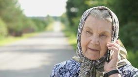Mogna samtal för gammal kvinna genom att använda smartphonen utomhus stock video