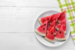 Mogna skivor av vattenmelon på en vit platta på en vit träbakgrund Royaltyfri Bild