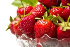 Mogna smakliga jordgubbar i en glass vas med gröna sidor Arkivbilder