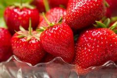Mogna smakliga jordgubbar i en glass vas med gröna sidor Arkivfoton