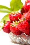 Mogna smakliga jordgubbar i en glass vas med gröna sidor Arkivbild