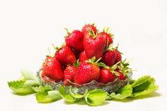 Mogna smakliga jordgubbar i en glass vas med gröna sidor Royaltyfri Fotografi