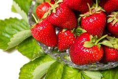 Mogna smakliga jordgubbar i en glass vas med gröna sidor Royaltyfria Bilder