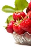 Mogna smakliga jordgubbar i en glass vas med gröna sidor Royaltyfria Foton