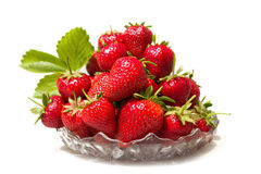 Mogna smakliga jordgubbar i en glass vas med gröna sidor Fotografering för Bildbyråer