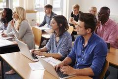 Mogna studenter som sitter på skrivbord i vuxenutbildninggrupp arkivfoto