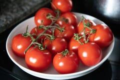 Mogna tomater för vinranka i en vit bunke på en graniträknare royaltyfri foto