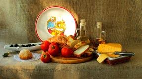 Mogna tomater, hemlagat bröd, ost och oliv Fotografering för Bildbyråer