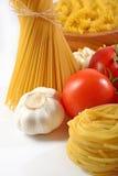 Mogna tomater, okokt italiensk pasta och vitlök på en vit Arkivfoto