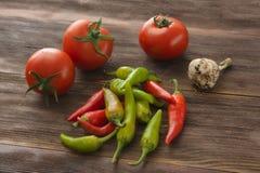 Mogna tomater, peppar för varm chili, vitlök på en trätabell Royaltyfri Fotografi