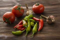 Mogna tomater, peppar för varm chili, vitlök på en trätabell Royaltyfri Foto