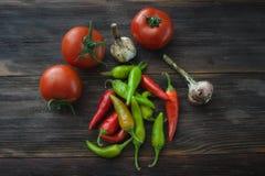 Mogna tomater, peppar för varm chili, vitlök på en trätabell Royaltyfri Bild