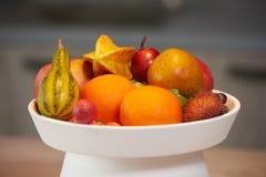 Mogna tropiska frukter i en vit maträtt Arkivfoton