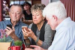 Mogna vänner i kaffehus med elektronik royaltyfri foto