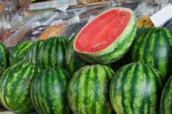 Mogna vattenmelon, saftiga vattenmelon, vattenmelon i marknaden per stycke av vattenmelon med en sten, vattenmelonbakgrund fotografering för bildbyråer