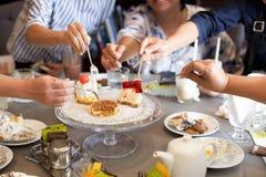 Mogna vänner som har kakan och drinken på födelsedag Royaltyfri Foto
