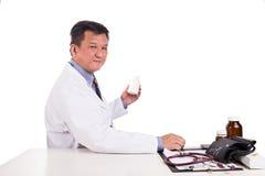 Mognad asiatisk placerad behin för praktiserande läkare hållande medicin royaltyfri fotografi