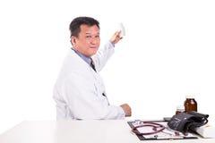 Mognad asiatisk placerad behin för praktiserande läkare hållande medicin royaltyfri foto
