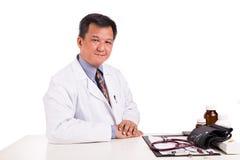 Mognad asiatisk praktiserande läkare som placeras bak skrivbordet arkivfoto