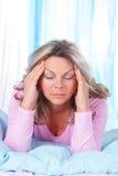 Mognad kvinna i säng med stark huvudvärk Arkivfoton