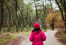 Mognad kvinna som fotvandrar i skogen arkivbild