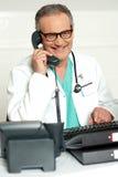 Mognad läkare som meddelar på telefonen royaltyfria bilder