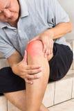 Mognad man som lider den smärtsamma knäleden som placeras på moment Royaltyfri Foto