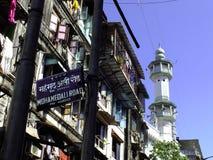 Mohamedali Road in Mumbai, India. Panel indicating landmark road in Mumbai, with minaret in the background Royalty Free Stock Images