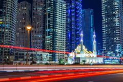 Mohammed Bin Ahmed Almulla mosque with buidings and light trails at night in Dubai. United Arab Emirates stock image