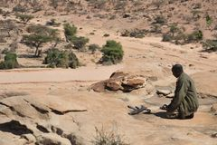 Mohammedan prayer. Somalia. LAS GIL, SOMALIA - JANUARY 9, 2010: Complex of caves with petroglyphs is the most significant monument of the epoch of the neolith in Royalty Free Stock Photos