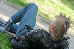 Mohawk hairstyle. A punker with mohawk style haircut sitting on a grass Royalty Free Stock Photography