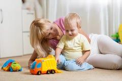 Moher e seus jogos do filho da criança com os brinquedos do carro em sua sala confortável do childrem foto de stock royalty free
