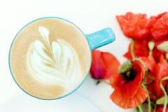 Mohnblumenblumen und blaue Schale Cappuccino auf weißer Tabelle Stockfoto