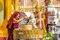 Moine bouddhiste arrosant la pagoda de Shwedagon de statue de Bouddha Photographie stock
