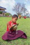 Moine bouddhiste de jeune novice non identifié dans des robes longues rouges traditionnelles pratiquant en jouant l'instrument de photo libre de droits
