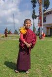 Moine bouddhiste de jeune novice non identifié dans des robes longues rouges traditionnelles se tenant devant un monastère dans P photographie stock libre de droits