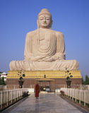 Moine bouddhiste et statue géante de Bouddha images stock
