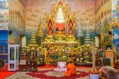 Moine bouddhiste méditant devant l'image d'or de Bouddha Image stock