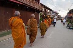 Moine bouddhiste marchant pour laisser des personnes mettre des offres de nourriture dans un alm Images libres de droits