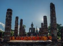 Moine bouddhiste priant devant l'image de Bouddha Photo libre de droits