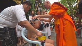 Moine bouddhiste rasant la tête d'un garçon pour le préparer pour le novice banque de vidéos