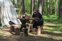 Moine dans des vêtements médiévaux attendant le dîner dans le camp photos stock