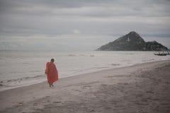 Moine de bouddhisme marchant à côté de la mer photographie stock