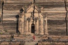 Moines avec les costumes traditionnels rouges et le parapluie rouge dans le temple bouddhiste photo libre de droits