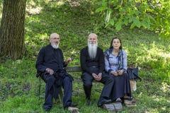 Moines et femme orthodoxes de paroissien en parc de Velika Remet photographie stock libre de droits