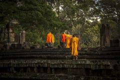 4 moines marchant au-dessus du mur antique Photographie stock libre de droits